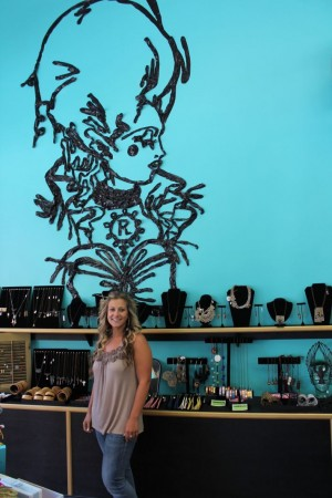 Rococo owner Courtney Coffey with duct tape mural
